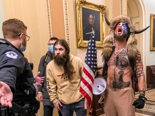 In this Jan. 6, 2021, file photo, supporters of President Donald Trump, including Jacob Chansley, right with fur hat, are confronted by U.S. Capitol Police officers outside the Senate Chamber inside the Capitol in Washington. Chansley previous served in the Navy for just more than two years, according to service records. (Manuel Balce Ceneta/AP)