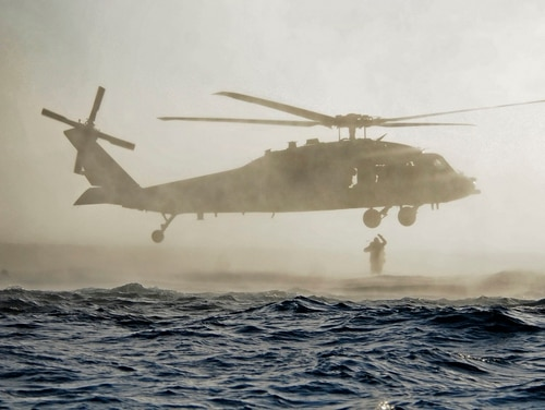 A U.S. Navy SEAL jumps out of an SH-60 Sea Hawk helicopter off the coast of San Diego. (US Navy photo by MC1 Michael Russell)