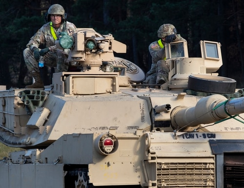 Members of the U.S. Army's 1st Armored Battalion of the 9th Regiment, 1st Division, out of Fort Hood, Texas, sit on a Abrams battle tank after arriving at the Pabrade railway station in Lithuania, about 30 miles north of the capital Vilnius, Oct. 21, 2019. (Mindaugas Kulbis/AP)