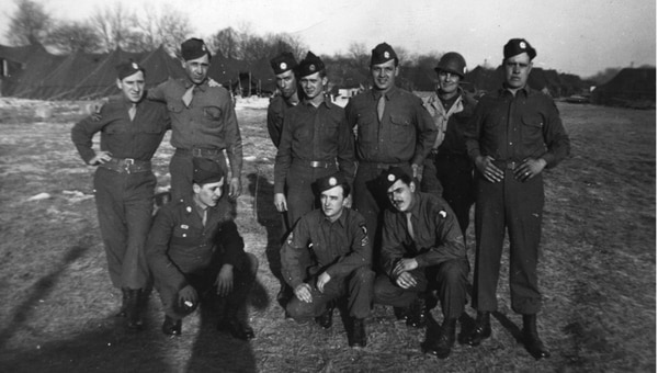 Pfc. Lawrence Boudreaux (second from left, standing) with members of his unit, the 321st Glider Field Artillery Battalion at Whatcombe Farms in England during World War II.