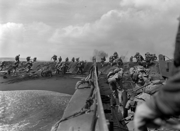 In the Pacific theater of World War II, U.S. Marines hit the beach and charge over a dune on Iwo Jima, Feb. 19, 1945, the start of one of the deadliest battles of the war against Japan. (Joe Rosenthal/AP)