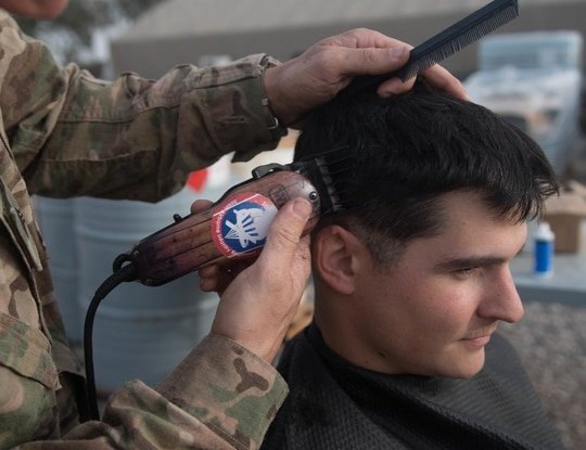 A soldier receives a haircut from another soldier while deployed to the Iraq and Syria area of operations on March 12, 2017. (Staff Sgt. Alex Manne/Army)