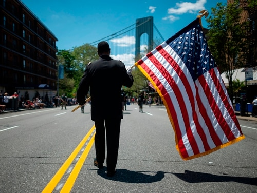 A veteran carries an American flag as he marches on the street May 27, 2019, during the 152nd Memorial Day parade in the New York City borough of Brooklyn. (Johannes Eisele/AFP via Getty Images)