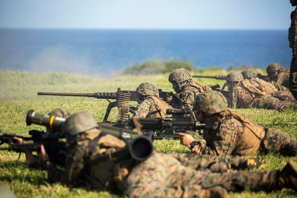Marines with second platoon, Bravo Company, 3rd Reconnaissance Battalion, 3rd Marine Division, fire at lead targets with multiple weapons systems as they work through a scenario to flank the