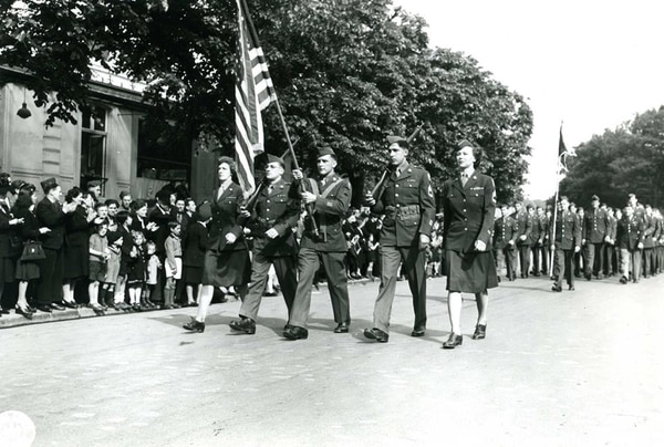 French civilians in Reims, France, the site of the German surrender on May 7, 1945, applaud American soldiers and WACs on parade during V-E Day celebration. (Army)