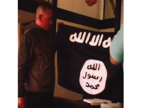 In this July 8, 2017, file image taken from FBI video and provided by the U.S. Attorney's Office in Hawaii, Army Sgt. 1st Class Ikaika Kang holds an Islamic State group flag after allegedly pledging allegiance to the terror group at a house in Honolulu. (FBI/U.S Attorney's Office, District of Hawaii via AP)