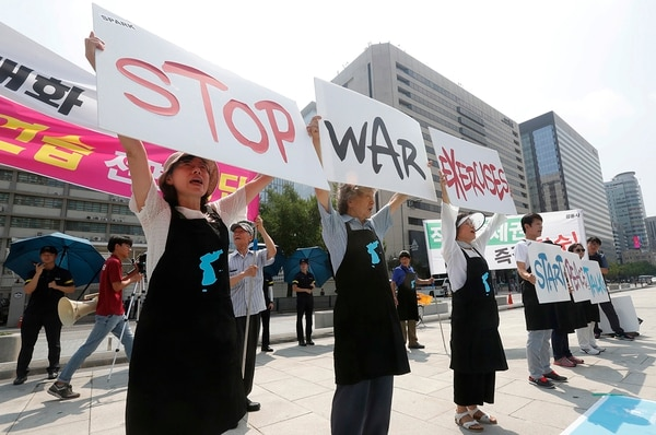 Protesters hold up placards to oppose planned joint military exercises between South Korea and the United States near the U.S. Embassy in Seoul, South Korea, Monday, Aug. 5, 2019. (Ahn Young-joon/AP)