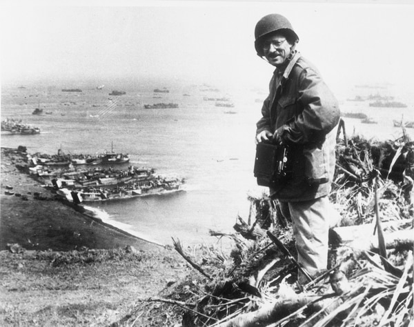 In this March 1945 photo, Joe Rosenthal, an Associated Press photographer, is shown with his camera equipment looking over Iwo Jima, Japanese volcano island during World War II. (U.S. Marine Corps via AP, File)
