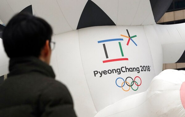 In this Dec. 29, 2017, photo, a man walks by the official emblem of the 2018 Pyeongchang Olympic Winter Games, in downtown Seoul, South Korea.(Lee Jin-man/AP)