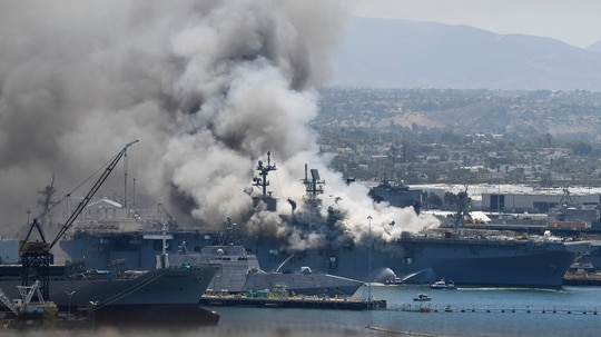 Smoke rises from the amphibious assault ship Bonhomme Richard Sunday after an explosion and fire on board the ship at Naval Base San Diego. (Denis Poroy/AP)