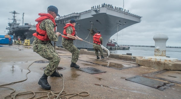 Sailors from the nearby aircraft carrier Abraham Lincoln pull on lines from the sister flattop Harry S. Truman at Norfolk Naval Station, July 21. The Navy will extend the careers of deckplates if they volunteer for sea duty. (Mark D. Faram/staff)