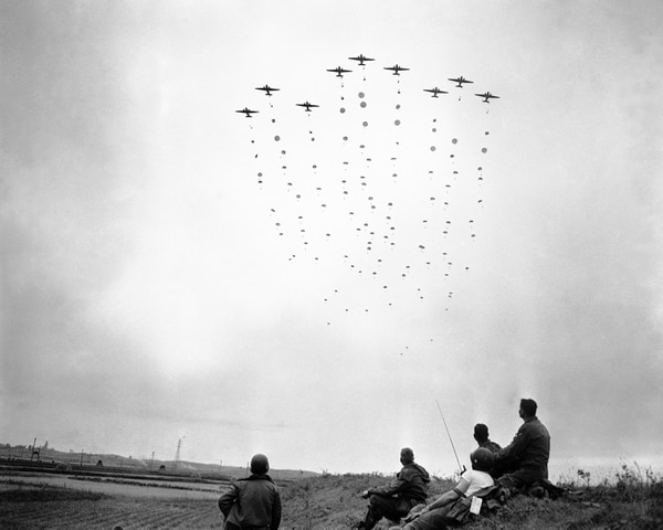 U.S. paratroopers leave their planes in a mass drop behind enemy lines in the Sunchon area of North Korea on Oct. 25, 1950 during an operation designed to block the escape route of the retreating Chinese and to attempt to rescue American prisoners. Members of an advance party (foreground) watch the landing. (AP Photo/Max Desfor