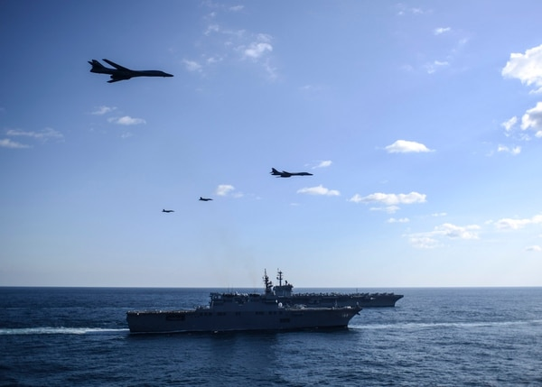 Two B-1B Lancer bombers and two F/A-18 Super Hornet strike fighters fly in formation over the Japan Maritime Self-Defense Force Hyuga-class helicopter destroyer JS ISE (DDH-182), front, and the U.S. Navy Nimitz-class aircraft carrier USS Theodore Roosevelt (CVN 71). The USS Ronald Reagan (CVN 76), USS Theodore Roosevelt (CVN 71) and USS Nimitz (CVN 68) Strike Groups are underway and conducting operations in international waters as part of a three-carrier strike force exercise on Nov. 12, 2017. (MC2 Holly L. Herline/Navy)