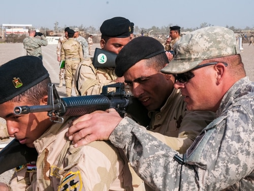 Sgt. David Kappel, an infantry trainer assigned to 1st Armored Brigade Combat Team, 1st Infantry Division, adjusts the rifle of an Iraqi army trainee as he instructs them how to properly