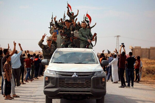 People welcome Syrian troops as they enter the town of Ein Issa, north of Raqqa, Syria, Monday, Oct 14, 2019. (SANA via AP)