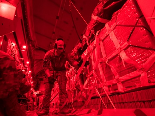 Senior Airman Jeremy Kosick, 816th Expeditionary Airlift Squadron instructor loadmaster, checks the cargo straps covering container delivery system bundles on a C-17 Globemaster III before an airdrop over Afghanistan, May 10. (Staff Sgt. Keith James/Air Force)