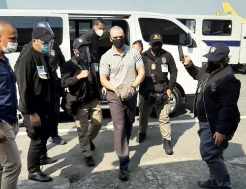 U.S. Marine Lance Cpl. Joseph Scott Pemberton, center, is escorted as he arrives at the airport before boarding a U.S. military plane in Manila, Philippines, Sunday, Sept. 13, 2020. (Bureau of Immigration PIO via AP)