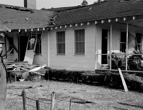 C. B. Gregg looks at the bomb damaged home of his brother Walter Gregg who was injured after an Air Force bomb hit about 100 yards away on March 12, 1958, in Florence, S.C. (AP Photo)