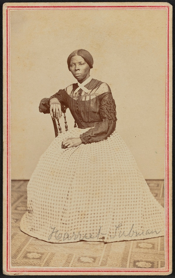 Harriet Tubman (1822-1913) at midlife. She is seated, turned toward the left. One hand rests on the back of a wooden chair, another rests in her lap. (Benjamin F. Powelson, now in the collections of the Library of Congress)