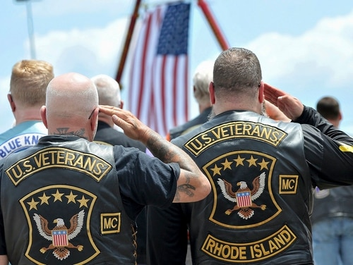Members of the U.S. Veterans Motorcycle Club salute the flag during the playing of the National Anthem at the beginning of a memorial and remembrance service for seven motorcyclists and spouses who died in the June, 2019 crash. (Mark Stockwell/The Sun Chronicle via AP)