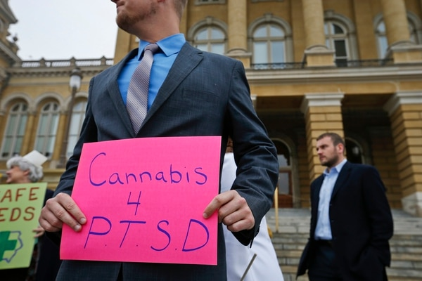 In this Tuesday, April 7, 2015, file photo, a Marine veteran holds a sign to show support for cannabis for post traumatic stress disorder sufferers, outside the State Capitol in Des Moines, Iowa. (Michael Zamora/The Des Moines Register via AP)