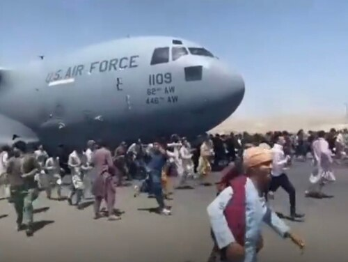 Afghans cling to a U.S. Air Force C-17 as it takes off from a runway in Kabul. (Screenshot via Twitter)