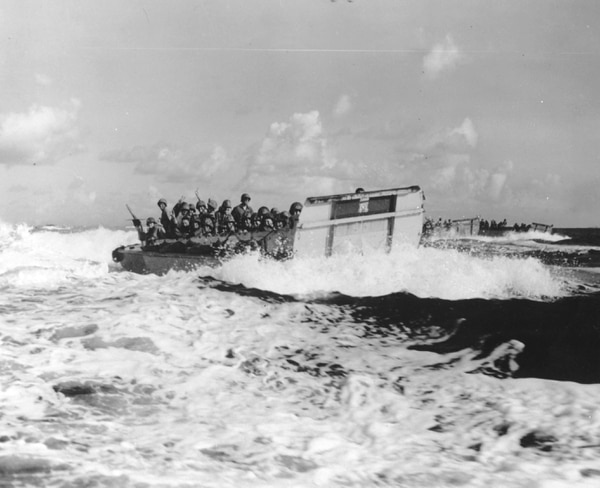FILE - In this in June 1944 filr photo, United States landing craft loaded with troops and equipment churn through heavy seas bound for the beaches of Saipan, Mariana Islands. A new book by a Texas-based military history writer tells the story of one of World War II's bloodiest battles and the role a New York National Guard unit played in the fighting. (AP Photo, File)