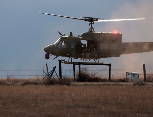 A 37th Helicopter Squadron UH-1N Bell Helicopter prepares to land and drop off 790th Missile Security Forces Squadron Tactical Response Force Airmen April 14, 2016, outside a launch facility in the F.E. Warren Air Force Base, Wyo., Missile Complex. The 37th HS supports the mission of the 90th Missile Wing by providing aerial surveillance and emergency deployments of security response forces throughout the base and missile field. (U.S. Air Force photo by Senior Airman Brandon Valle)