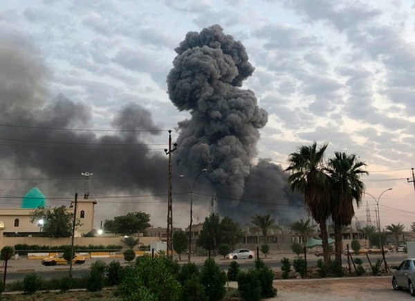 Plumes of smoke rise after an explosion at a military base southwest of Baghdad, Iraq., on Monday, Aug. 12, 2019. (Loay Hameed/AP)