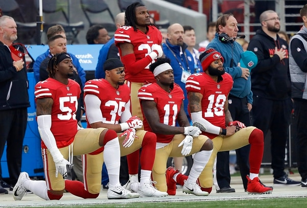 In this Dec. 24, 2017, file photo, San Francisco 49ers outside linebacker Eli Harold, from bottom left, kneels with safety Eric Reid, wide receiver Marquise Goodwin and wide receiver Louis Murphy during the national anthem before an NFL football game against the Jacksonville Jaguars in Santa Clara, Calif. (Marcio Jose Sanchez/AP)
