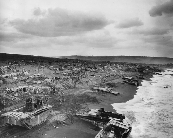 Original caption from 1945: This general view shows amtracs bogged down in the sands along the beaches of Iwo Jima after American invasion of the Japanese stronghold in 1945 during World War II. In the background, U.S. Marines and Coast Guard beach parties operate communications and command posts and fox hole