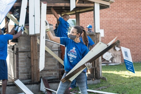 A volunteer helps demolish a damaged BBQ pit. The team rebuilt the framing, walls and windows on the pit, refurbishing the space to return to service for the Independence Heights community in Houston. (The Mission Continues)