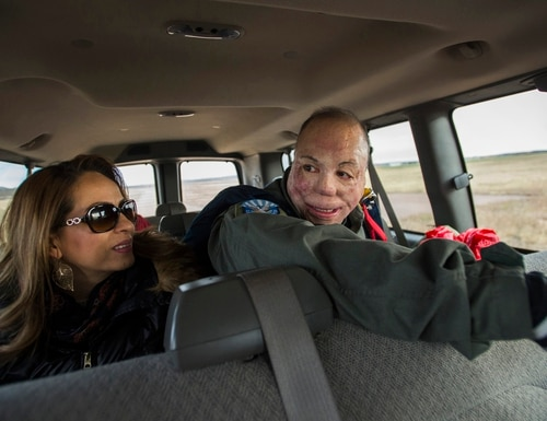 In this Saturday, Feb. 18, 2017 photo, Master Sgt. Israel Del Toro and his wife, Carmen, ride back to the parachute center after he made his first jump at the parachute training center on Air Force Academy in Colorado Springs, Colo. Del Toro was severely burned in a roadside bomb blast in Afghanistan in December 2005. In 2010, Del Toro became the first airman with a 100 percent disability rating to be allowed to re-enlist and Saturday he jumped for the first time since his injury. (Christian Murdock /The Gazette via AP)