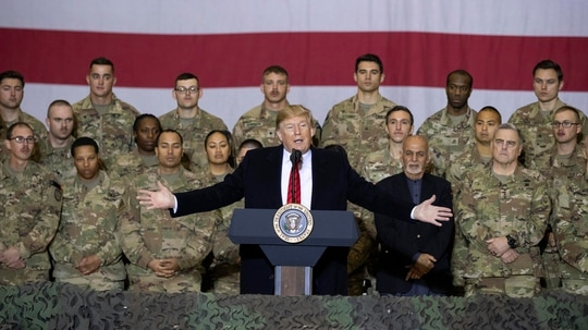 President Donald Trump, center, with Afghan President Ashraf Ghani and Joint Chiefs Chairman Gen. Mark Milley, behind him at right, while addressing members of the military during a surprise Thanksgiving Day visit, Thursday, Nov. 28, 2019, at Bagram Air Field, Afghanistan. (Alex Brandon/AP)