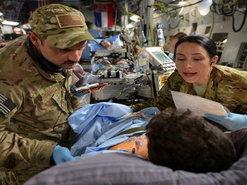 Capt. Mario Ramirez and Capt. Suzanne Morris, members of the 455th Expeditionary Aeromedical Evacuation Squadron Critical Care Air Transport Team, care for a patient during a flight out of Bagram Airfield, Afghanistan, March 21, 2013. (Sr. Amn. Chris Willis/ Air Force)
