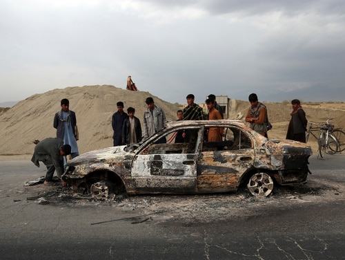 In this April 9, 2019, file photo, Afghans watch a civilian vehicle burnt after being shot by U.S. forces following an attack near the Bagram Air Base, north of Kabul, Afghanistan. (Rahmat Gul/AP)