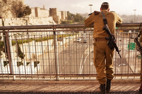 JERUSALEM, ISRAEL - NOVEMBER 28: A member of the Israeli Defense Forces (IDF) pauses in a park near the Old City on November 28, 2014 in Jerusalem, Israel. Nine Israelis have been killed in a series of stabbings, shootings and hit-and-run attacks in Jerusalem over the past month, unsettling the ancient city of Jerusalem where Jews, Christians and Muslims have lived side by side for thousands of years. The tension and violence on the streets of the city is threatening to further isolate communities and to encourage extremist politicians to exploit the situation. (Photo by Spencer Platt/Getty Images)