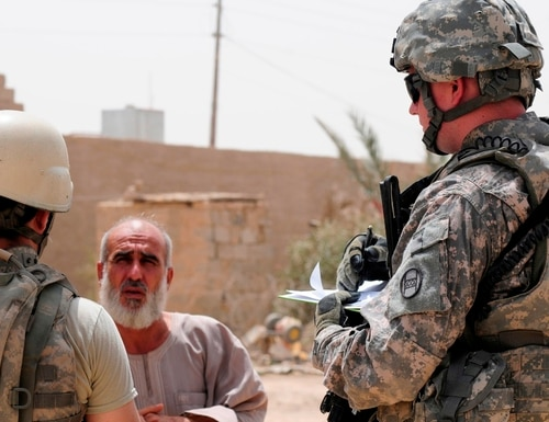 A U.S. soldier asks questions of an Iraqi villager through an interpreter in Yaaskhdir, in the Radwaniyah District, south of Baghdad, during a joint Iraqi and U.S. patrol, Aug. 3, 2009. (Army)