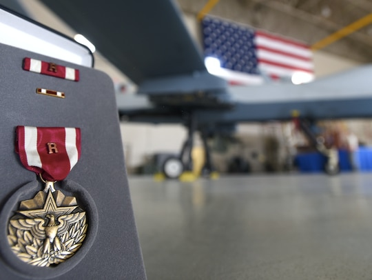 """An Air Force Meritorious Service Medal with attached remote """"R"""" device is displayed in front of an MQ-9 Reaper July 9 at Creech Air Force Base, Nevada. (Senior Airman James Thompson/Air Force)"""