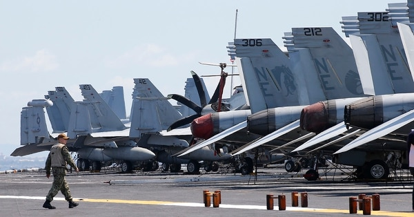 A sailor walks past military aircraft on the flight deck of the USS Carl Vinson aircraft carrier anchors off Manila, Philippines, for a five-day port call along with guided-missile destroyer USS Michael Murphy, Saturday, Feb. 17, 2018. Lt. Cmdr. Tim Hawkins told The Associated Press that American forces will continue to patrol the South China Sea wherever international law allows when asked if China's newly built islands could restrain them in the disputed waters. (Bullit Marquez/AP)