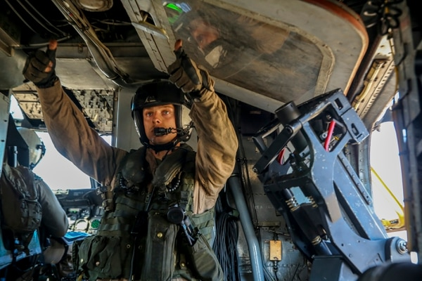 Lance Cpl. Dillon Semolina, crew chief with the Aviation Combat Element, Marine Rotational Force--Darwin, gives hand signals before taking off as a part of a training exercise aboard Mount Bundey Training Area, July 9, 2014. The rotational deployment in Darwin enables Marines to more effectively train, exercise and operate with partners, enhances regional security, and builds capacity to respond more rapidly to natural disasters and crises throughout that region.