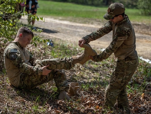 U.S. Air Force Staff Sgt. Trevor McBride, right, helps Senior Airman Keifer Bowes remove his boots after conducting the 10-mile road march. One of the military's main boot suppliers was exposed for selling Chinese knock-offs to the military. (Staff Sgt. Pablo N. Piedra/Army)