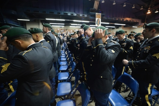 Soldiers from the U.S. Army John F. Kennedy Special Warfare Center and School, don their green berets during a Regimental First Formation at the Crown Arena in Fayetteville, North Carolina September 26, 2019. The ceremony marked the completion of four phases of the Special Forces Qualification Course where Soldiers earned the honor of wearing the green beret, the official headgear of Special Forces. (U.S. Army photo illustration by K. Kassens)