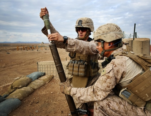 Lance Cpl. Dale Parrott, a mortarman serving with India Company, 3rd Battalion, 7th Marine Regiment, fires a 60mm mortar while Lance Cpl. Nathanial Sui holds the mortar tube steady during unknown distance live-fire training at Camp Leatherneck, Helmand province, Afghanistan, Nov. 24, 2013. Parrott is a 22-year-old native of Humble, Texas. Sui is a native of Hayward, Calif. (U.S. Marine Corps photo by Cpl. Corey Dabney/Released)