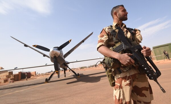 A French soldier of the aerial detachment of the Operation Barkhane stands guard near a Reaper drone at the Nigerian military airport Diori Hamani in Niamey on January 2, 2015. (DOMINIQUE FAGET/AFP/Getty Images)