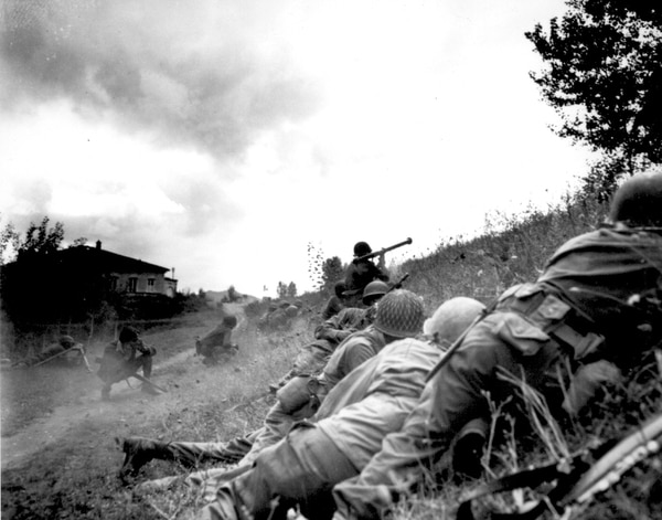 This African American combat patrol advanced three miles north of Lucca (furthermost point occupied by American troops) to contact an enemy machine gun nest on Sept. 7, 1944. Here a bazooka-man cuts loose at the target some 300 meters distant. (National Archives)