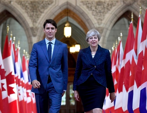 Prime Minister Justin Trudeau, left, and British Prime Minister Theresa May walk in the Hall of Honour on Parliament Hill in Ottawa, Ontario, during a Sept. 18, 2017, visit. (Justin Tang/The Canadian Press via AP)