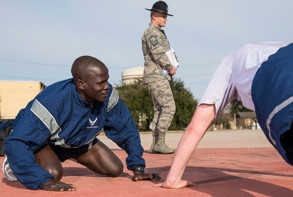 Guor Maker, a trainee at Air Force basic military training, supports a wingman taking a physical fitness test Jan. 30 at Join Base San Antonio-Lackland, Texas. (Airman 1st Class Dillon Parker/Air Force).