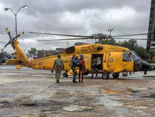 Master Sgt. Jamie Blevins and Tech. Sgt. Joshua Busch of the Kentucky Air National Guard's 123rd Special Tactics Squadron establish and control a helicopter landing zone in the parking lot of a library in Pasadena, Texas, on Aug. 29. (Air National Guard)