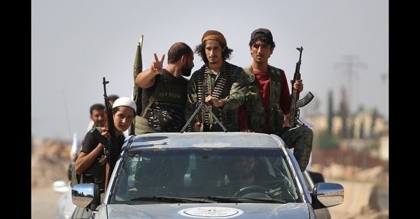 Syrian rebel fighters from the recently formed National Liberation Front parade following military training at an unknown location in the northern countryside of the Idlib province on Sept. 11, 2018, in anticipation for an upcoming government forces offensive. (Aaref Watad/AFP via Getty Images)